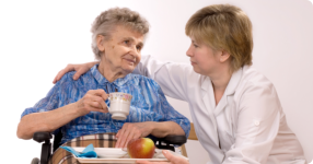 nurse is serving food to an elderly woman